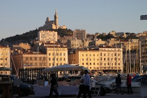 An evening view of Marseille's Vieux Port with the city's iconic Notre-Dame de la Garde highlighting the scene.