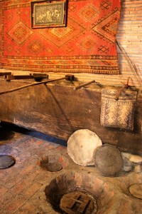 A display of equipment used in traditional Georgian winemaking, seen at Wine House Gurjaani. Grapes are crushed in a wooden vat, seen against the wall, then drained into buried clay pots. The pots here are under a brick floor with only lids visible.
