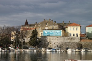 View of walls surrounding Zadar's Old Town — and a very current advertiser's billboard. The natural harbor between the Zadar peninsula and mainland Zadar is in the foreground.