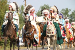 Young men riding in the horse parade at the Crow Fair in August 2013. Note the colorful mask on the horse at right.
