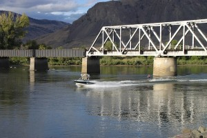 A water skier roars along the Thompson River, passing under a railroad bridge in Kamloops.