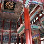 Interior of the king's audience hall at Gyeongbok Palace, with brightly painted wood ceiling elements and very red pillars.