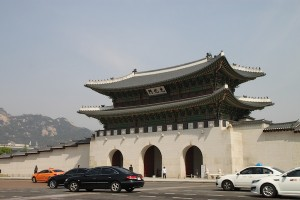 Gwanghwamun, entryway to Gyeongbok Palace in the middle of Seoul, with a mountain in the background at left.