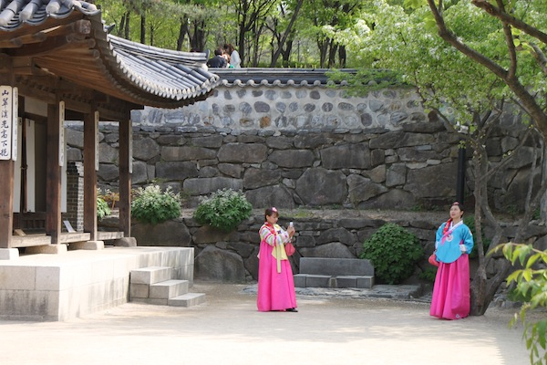Women in rented traditional Korean dresses enhance the look of traditional homes in the Namsangol Hanok Village.