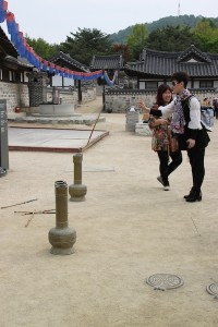 Visitors to Namsangol Hanok Village test their skills at an old Korean game that involves tossing arrows into a narrow-necked jar.