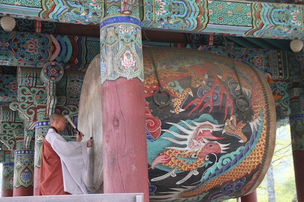A Haeinsa monk, using a very large hanging drum, calls fellow Buddhists to an evening service.