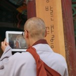 A Haeinsa monk films another who uses a drum to call fellow Buddhists to an evening service.