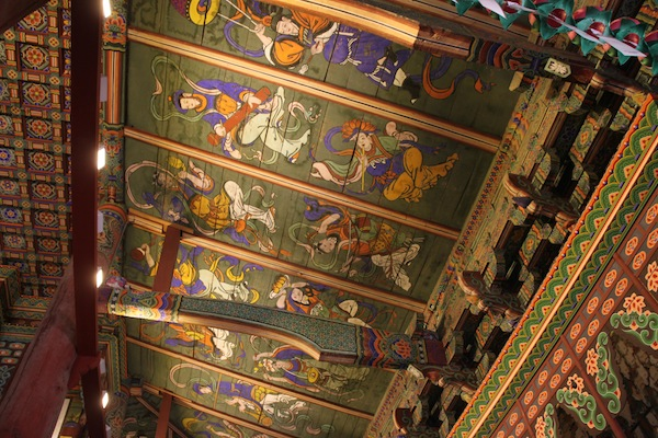 Fabulous characters painted on the ceiling inside the main hall of worship at Haeinsa Buddhist temple.