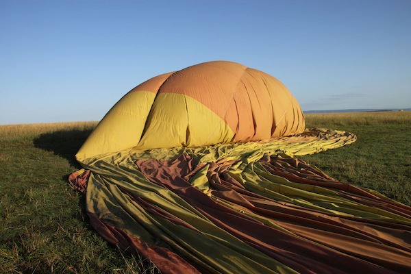 The flight completed, a hot-air balloon deflates on the ground.