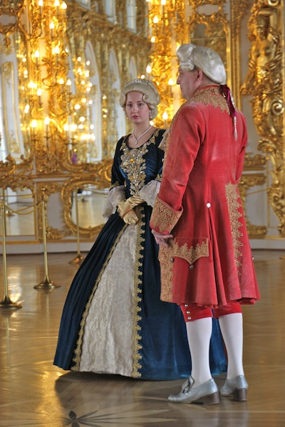 Couple in period costumes ready to pose for photos with tourists, for a price, inside Catherine Palace. They are in the Grand Hall.