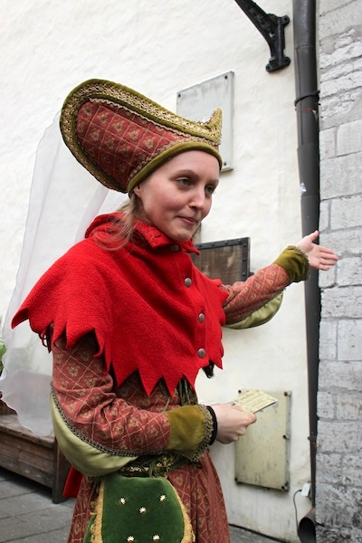 A staffer at Olde Hansa restaurant, in period costume, urging passersby to try the eatery.